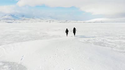 Mother And Son Plays Running In Winter Landscape