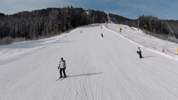 Thumbnail for Aerial View Lot of Skiers Go Down the Ski Slopes. Drone Flies Low Next To Skiers