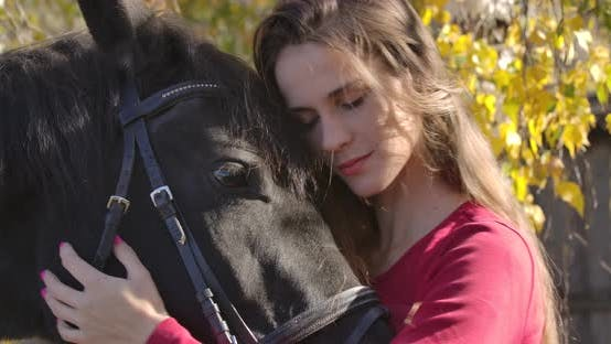 Thumbnail for Close-up Portrait of a Young Caucasian Girl Caressing Horse Face in the Autumn Forest and Smiling