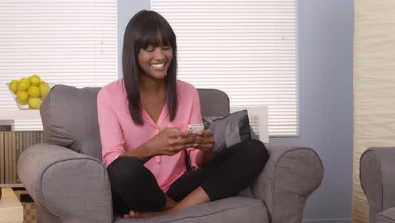 Thumbnail for Pretty african woman using smartphone at home