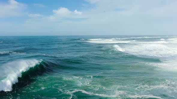 Thumbnail for Large Blue Ocean Waves Crash with Spray and Foam Forming a Rainbow, Aerial View