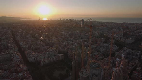 Flying over Barcelona and Sagrada Familia at sunset