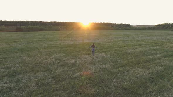 Thumbnail for Unrecognizable Woman Walking on the Field at Sunset Arms Outstretched