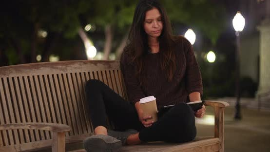 Thumbnail for Millennial woman on bench at night using tablet computer and drinking coffee
