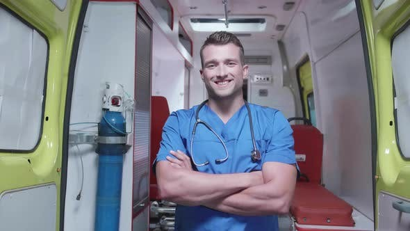 Thumbnail for Man in Medical Uniform Stand on the Background of Ambulance Car.