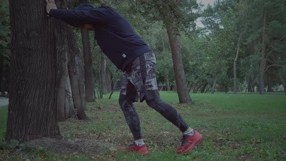 Thumbnail for Sportive man is stretching outdoors