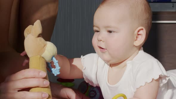Funny Happy Baby Girl Crawls with Toy Teething on Stomach and Sways on Knees in Bright Sunlight