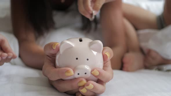 Mother and Two Children Saving Money To Piggy Bank. Family Earning Money for Future. Investment
