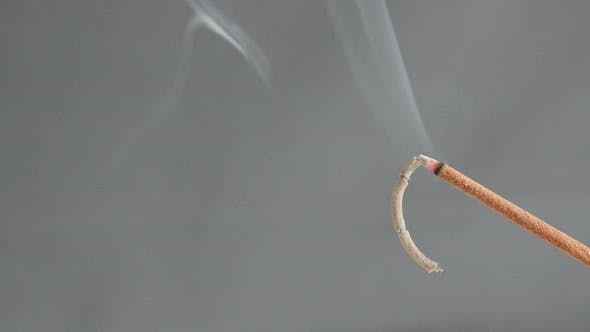 Burned  fragrant incense stick spreading smoke 4K 2160p 30fps UltraHD footage - Burning of aromatic
