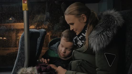 Thumbnail for Mom and Kid Playing on Mobile During Evening Bus Ride