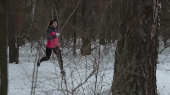 Thumbnail for Female Athlete Running Through Winter Forest