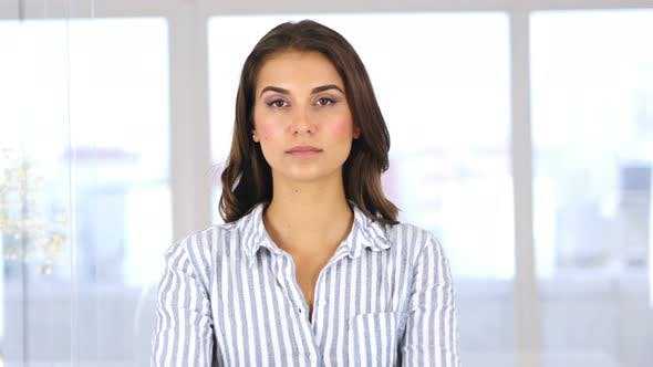 Thumbnail for Serious Young Hispanic Woman Looking at Camera in Office