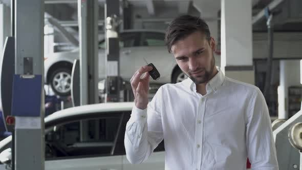Thumbnail for Young Handsome Man in Car Service Shop Showing His Car Keys and Smiling on the Background of His Car