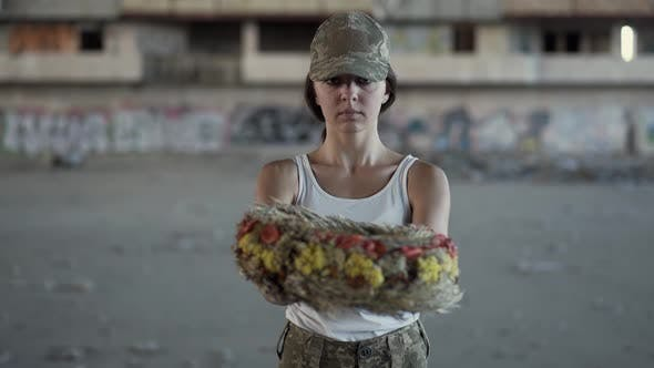 Cover Image for Portrait of a Beautiful Girl in a Camouflage Cap and White T-shirt Holding a Wreath Looking