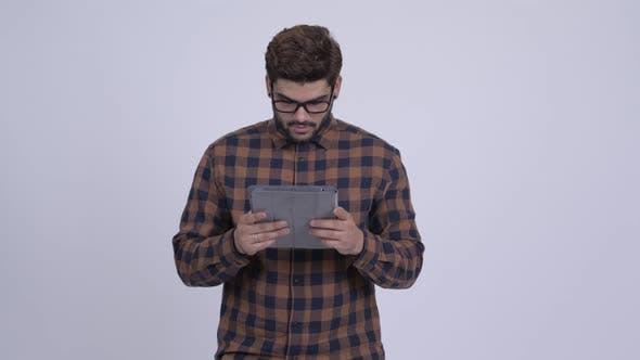 Cover Image for Young Bearded Indian Hipster Man Using Digital Tablet