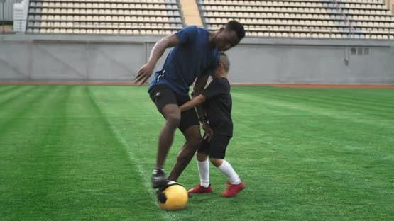 Boy Trying to Take Football Ball From Black Trainer