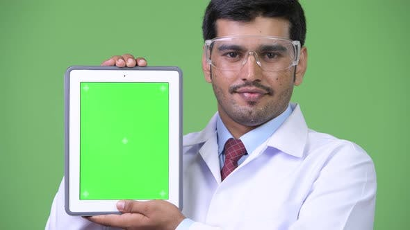 Thumbnail for Young Handsome Persian Man Doctor Wearing Protective Glasses Showing Digital Tablet