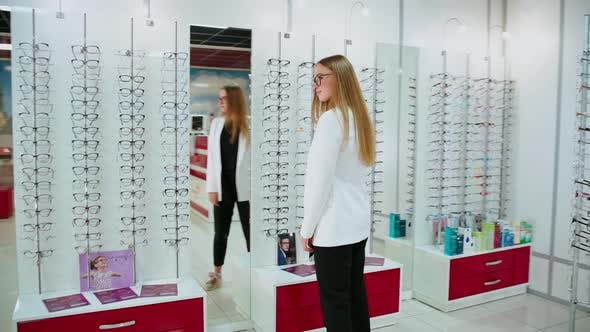 Thumbnail for Woman at optical store. Young woman checking her new glasses in mirror at optical store
