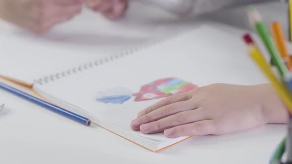 Close-up of Caucasian Child's Hands Drawing with Colorful Pencil in Exercise Book