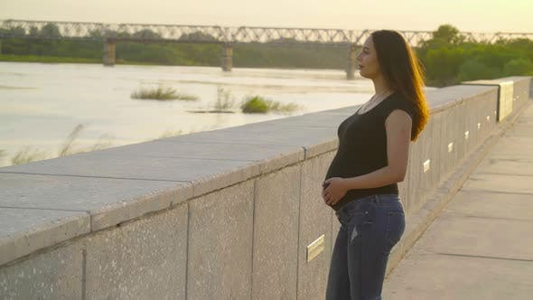Maternity and Pregnancy Concept. Young Happy Pregnant Woman in the Sunset