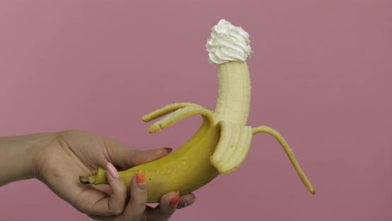 Woman Hand Holds Banana with Whipped Cream on Top of the Fruit