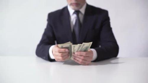 Reicher Mann zählt Bündel von Dollar-Banknoten, Geschäftsmann schätzt Einkommen