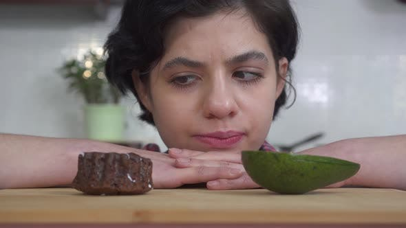 Thumbnail for Portrait of Young Hungry Girl Choosing Between Fresh Avocado and Tasty Brownie Cake and After Eating