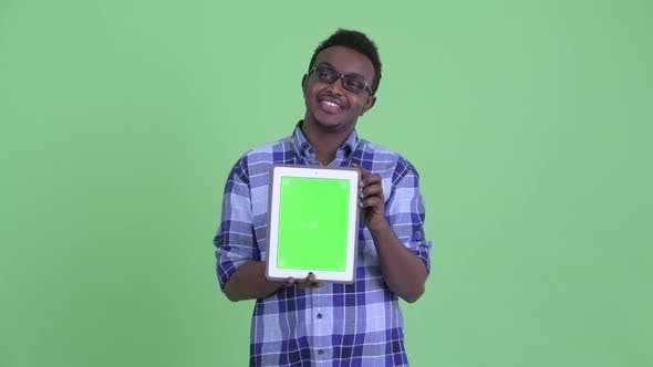 Thumbnail for Happy Young African Hipster Man Thinking While Showing Digital Tablet