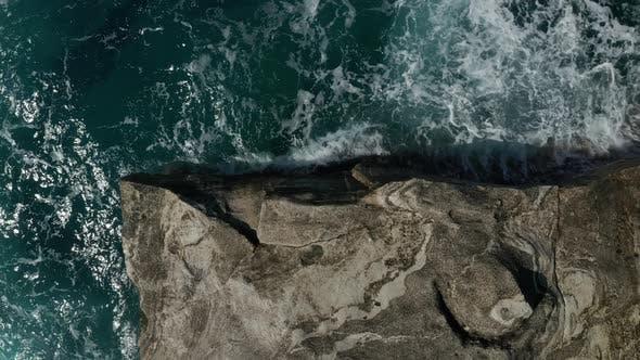 Aerial Overhead Top Down Birds Eye View of Big Ocean Waves Crashing on Rocks