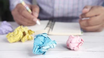 Crumpled Paper Ball and Man Writing on Notepad