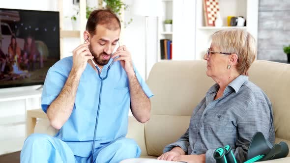 Thumbnail for Caucasian Male Doctor in Nursing Home Listening Old Woman Heartbeat