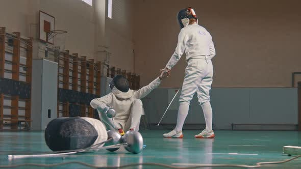Thumbnail for Two Young Women Fencers Having a Training in the Gym - Giving a Hand To Help To Stand Up