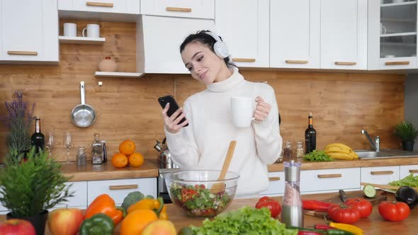 People And Technology Concept, Woman Dancing In Kitchen While Using Smartphone