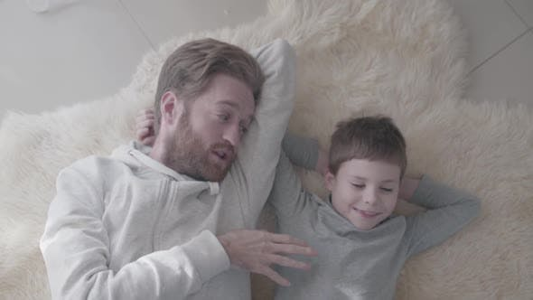 Father with Beard and His Little Son Lying at the White Fur Carpet and Have Interesting Conversation
