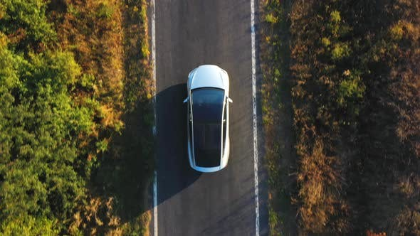 Thumbnail for Aerial Shot of Electrical Car Driving on Country Road at Summer Evening. New SUV Vehicle Moving Fast