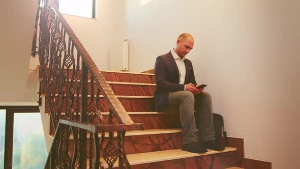 Thumbnail for Businessman Typing on Smartphone Sitting on Stairs
