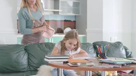 Thumbnail for Porträt von kaukasischen Schulmädchen tun Hausaufgaben am Tisch als Ihre Mutter kommen aus der