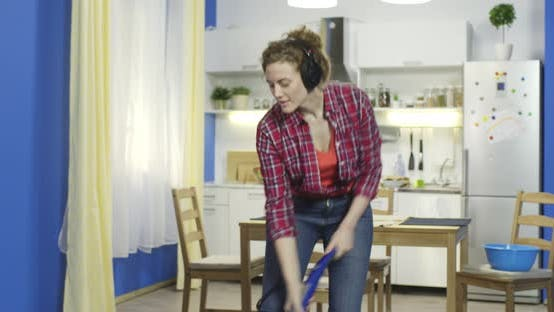 Thumbnail for Woman Cleans with Blue Vacuum and Sings Loudly