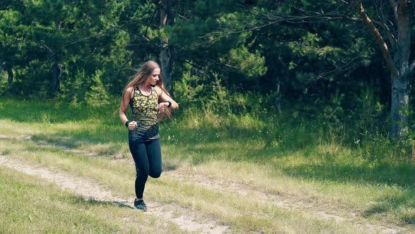 Thumbnail for Young Girl Goes in for Sports in the Morning, Runs Along a Pine Forest.