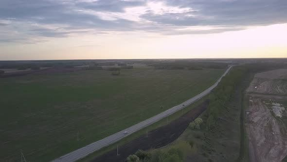 Thumbnail for Distant White Car Speeds Along Wide Highway at Twilight