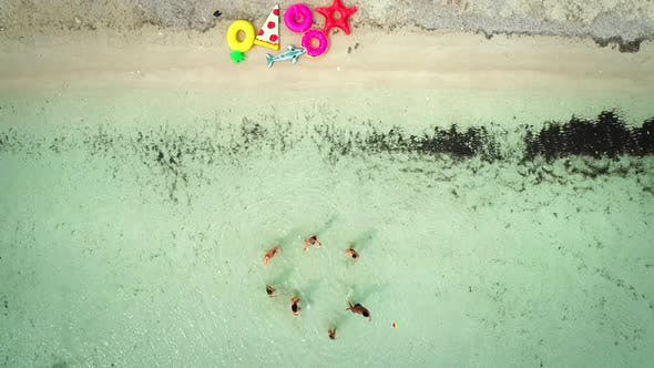 Cover Image for Aerial view of friends playing volleyball standing in sea by sandy beach.