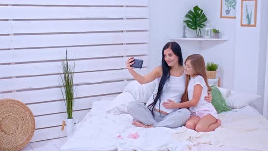 Happy Mother and Daughter Take Pictures at Home in the Bedroom, Take a Selfie on the Phone. Pregnant