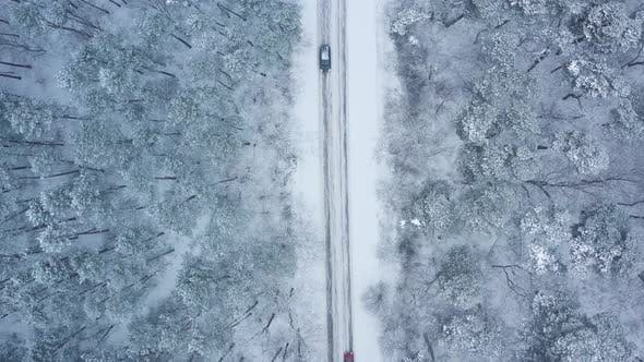 Top View of Traffic on a Road Surrounded By Winter Forest in Snowfall