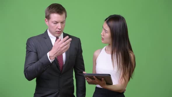 Thumbnail for Young Asian Businesswoman Showing Bad News To Young Businessman