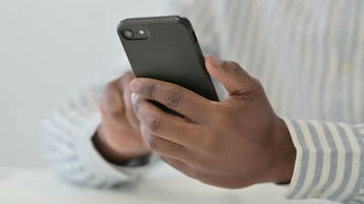 Close Up of African Man Using Smartphone Mobile