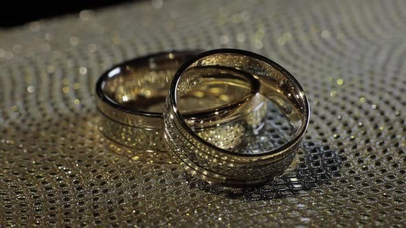 Thumbnail for Wedding Gold Rings Lying on Shiny Glossy Surface. Shining with Light