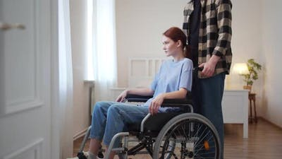 A Man is Driving His Girlfriend in a Wheelchair