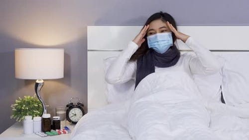 sick woman in medical mask is headache and suffering from virus disease and fever in bed