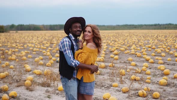 A Young Couple Stands Embracing in a Pumpkin Field
