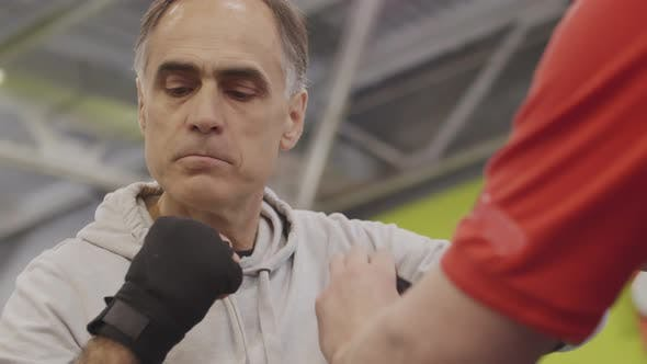Thumbnail for Trainer Helping Aged Man Preparing for Fight